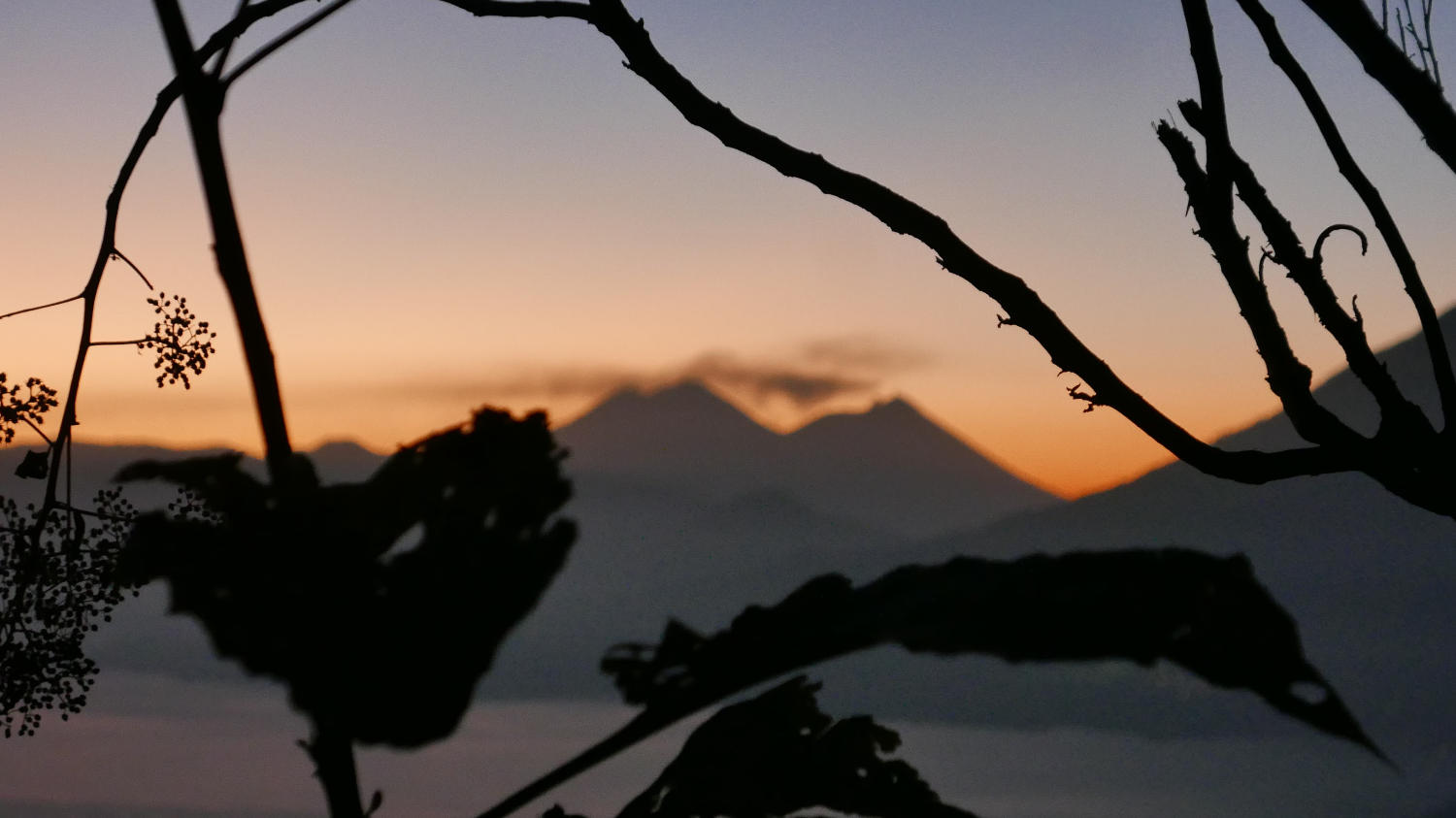 Just before sunrise at Lake Atitlan. Clouds hanging over Fuego volcano