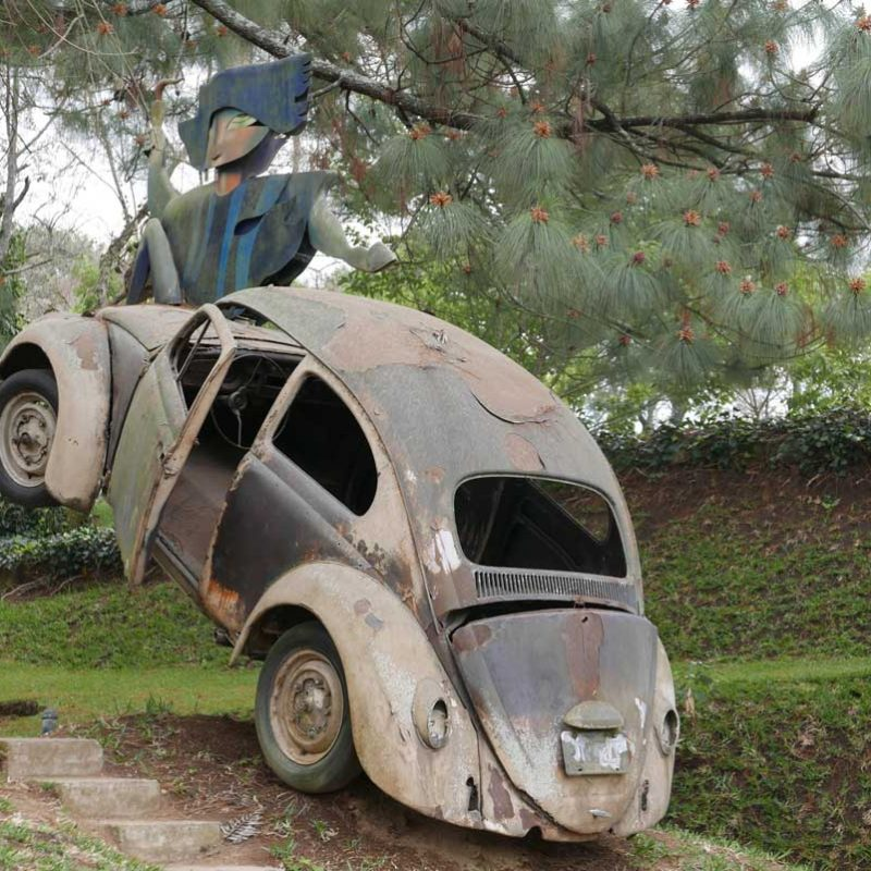 Crashed Volkswagen Beetle as a sculpture at Santo Domingo de Cerros near Antigua